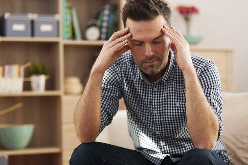 Zmęczony mężczyzna trzyma się za głowę