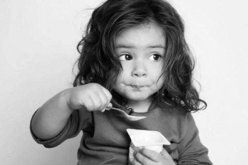 Poprawić koncentrację - dziewczynka je jogurt