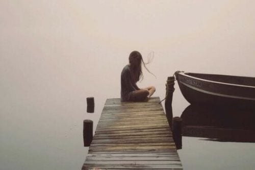samotna kobieta siedzi na molo nad jeziorem