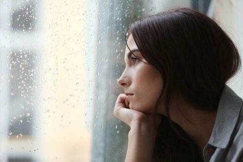 Smutna kobieta patrzy przez okno