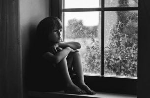 Smutne dziecko w oknie - brak uczuć u dzieci