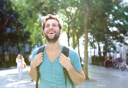 Szczęśliwy mężczyzna z plecakiem chodzi po mieście