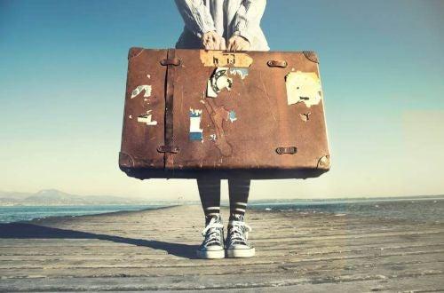 człowiek z wielką walizką stoi na molo