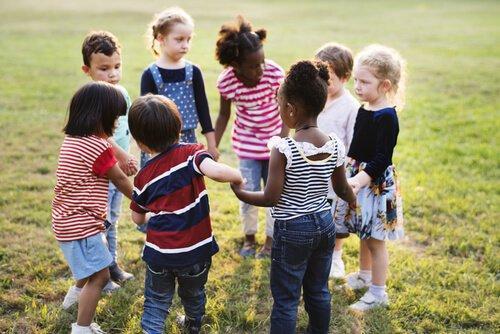 Dzieci trzymają się za ręce stojąc w kole