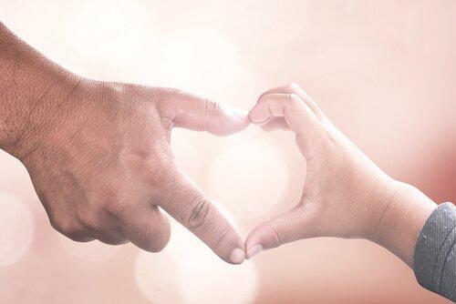 Dziecko i opiekun składają ręce w serce