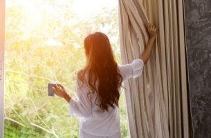 kobieta wyglądająca przez okno - wczesne wstawanie
