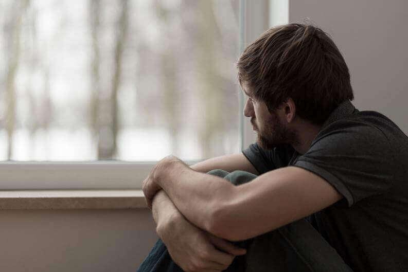 Mężczyzna siedzi przy oknie