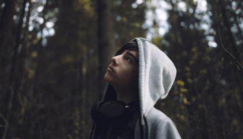 Myślący nastolatek w lesie.