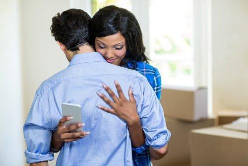 niewierność - mężczyzna obejmuje kobietę, któa patrzy na telefon