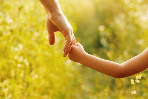 Ojciec trzymający za rękę córeczkę.