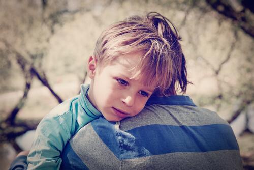 Samobójstwa nieletnich - smutny chłopiec w objęciach dorosłego człowieka