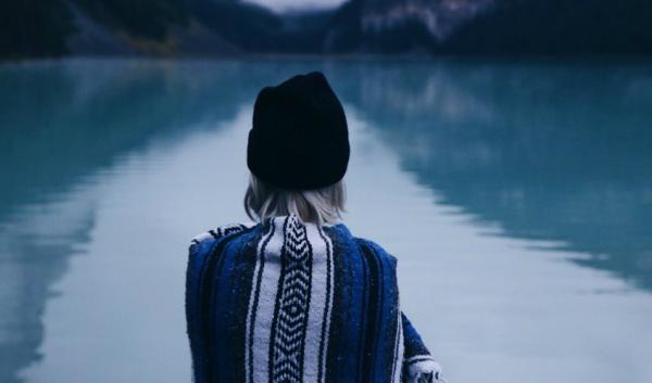 Smutna kobieta siedzi nad jeziorem