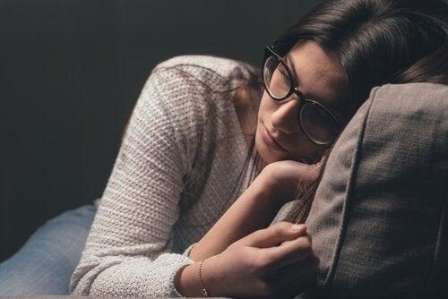 Smutna młoda kobieta na kanapie