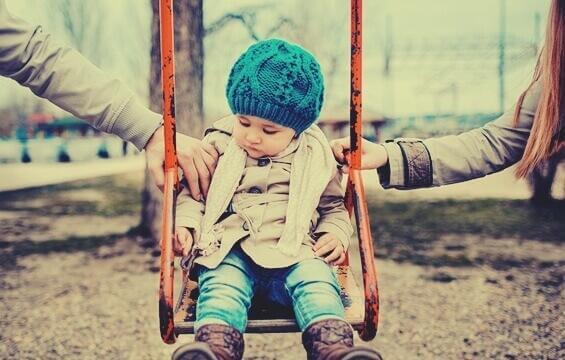 Dziecko na huśtawce trzymane przez dwoje rodziców - co-parenting