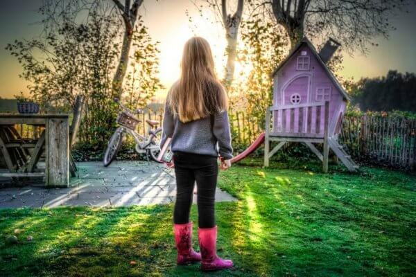 Dziewczynka i różowy domek do zabawy