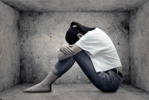 Kobieta siedzi w betonowej klatce