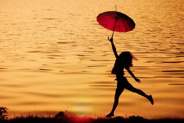 Kobieta biegnie z parasolem - pragmatyczny optymizm