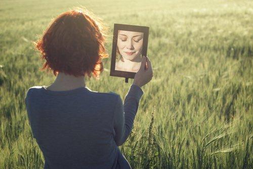 Kobieta na polu patrzy w małe lustro