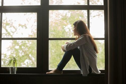 Smutna kobieta siedzi w oknie