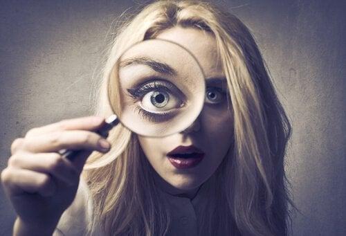 Kobieta patrzy przez lupę - zbytnia samokrytyka