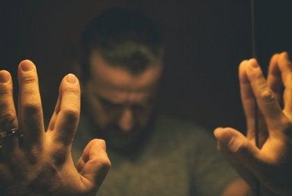 Załamany mężczyzna opiera się o lustro - iluzja przejrzystości