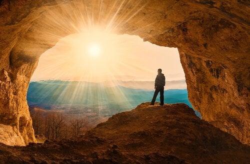 Człowiek stojący przy wejściu do jaskini.