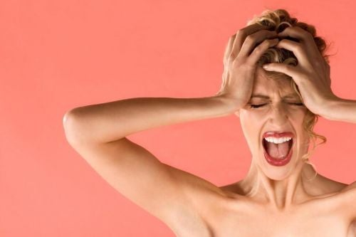Mizofonia - kobieta trzyma się za głowę i krzyczy