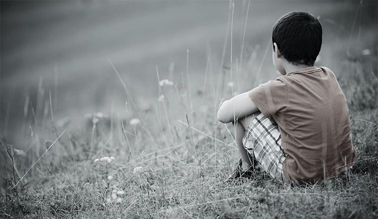 Smutny chłopczyk siedzi na trawie