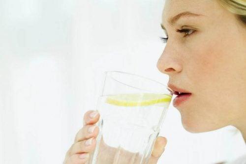 kobieta pije wodę z cytryną