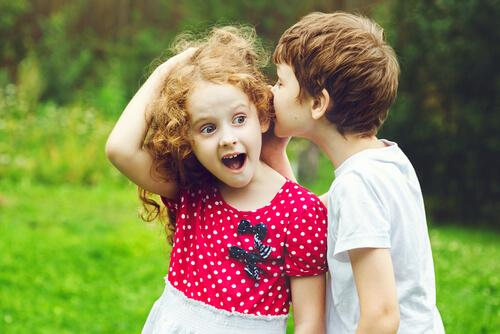 Chłopiec szepcze dziewczynce do ucha