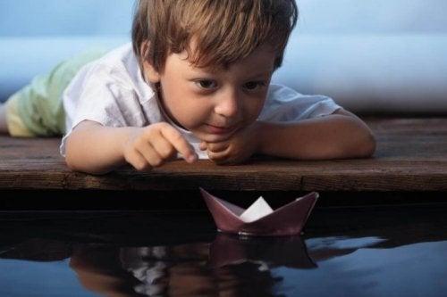 chłopiec z papierową łódką