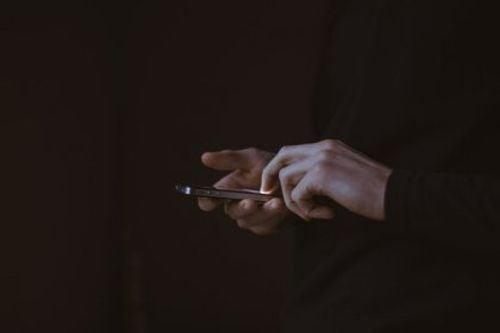 cyberprzemoc człowiek ze smartfonem w dłoniach