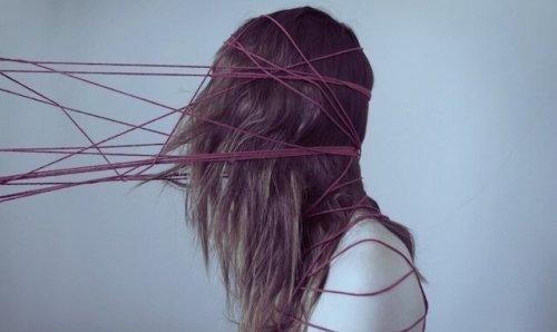 kobieta z głową obwiązaną sznurkami