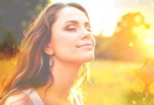 poddaj się chwili - kobieta z zamkniętymi oczami uśmiecha się