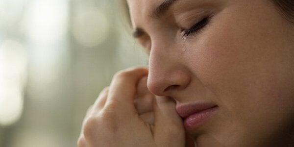 kobieta wysuszająca łzy