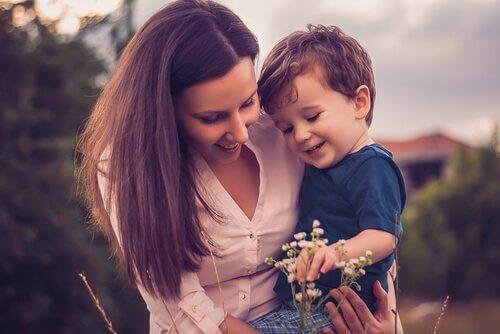 Mama trzyma syna na ręku i zbiera kwiaty