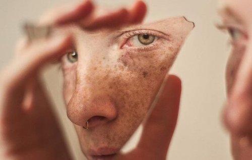 mężczyzna patrzy na swoją twarz w odłamku szkła