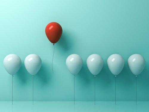 Normalność - czerwony balon pośród białych