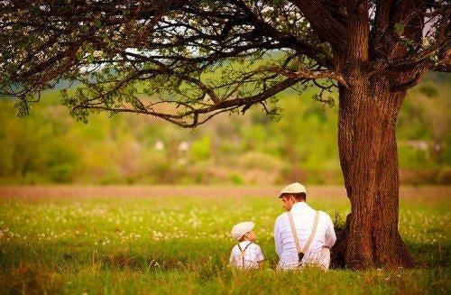 Ojciec i syn rozmawiają pod drzewem