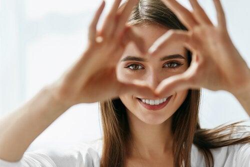 Kobieta układa serce z dłoni