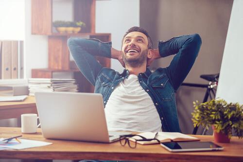 Szczęśliwy mężczyzna pokazujący że znalezienie szczęścia w pracy jest możliwe