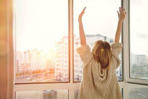 Zrelaksowana kobieta przeciąga się przy oknie