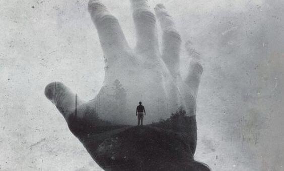 Szara dłoń na tle krajobrazu