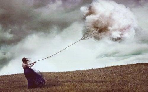 kobieta przeciągająca chmurę reprezentująca związek z samym sobą