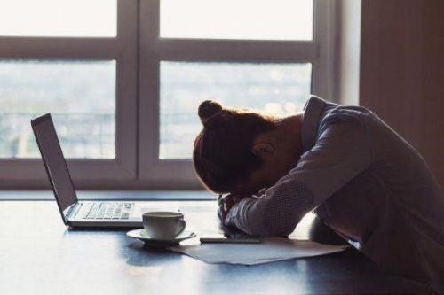 Smutna kobieta opiera głowę o biurko