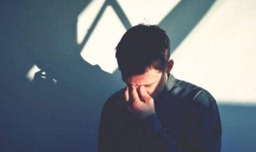 Smutny mężczyzna z rękami na twarzy