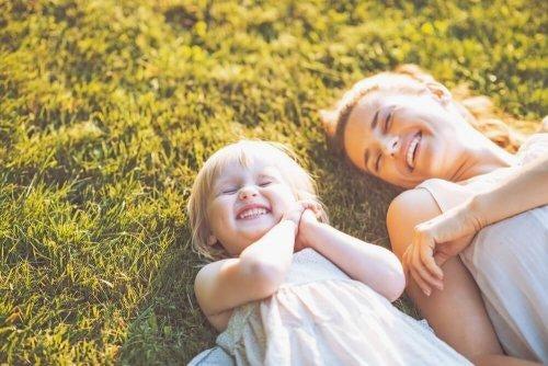 Córka i mama uśmiechają się na łące.