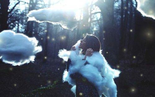 Kobieta w lesie w otoczeniu chmur