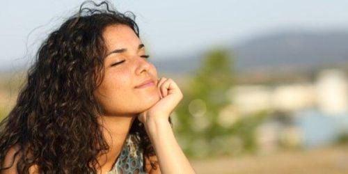 Kobieta z zamkniętymi oczami uśmiecha się