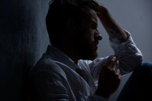 Smutny mężczyzna przy ścianie z fajką